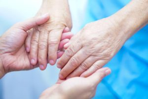 Caregiver holding hands with resident